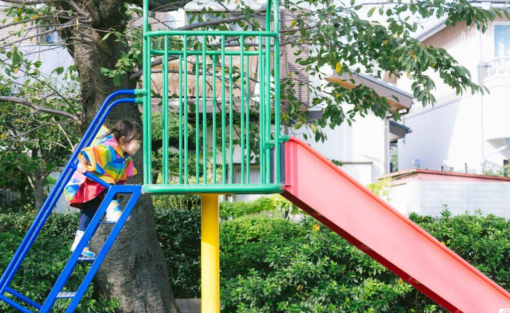 小さな女の子がカラフルなレインコートと長靴で滑り台に上っています。1人で滑れるかな。